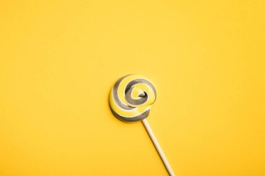 top view of delicious multicolored swirl lollipop on wooden stick on yellow background