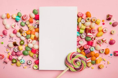 top view of delicious multicolored candies, lollipop and white card with copy space on pink background