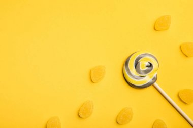 top view of delicious multicolored swirl lollipop on wooden stick and jellies on yellow background