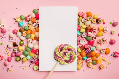 top view of delicious candies, lollipop and white card with copy space on pink background