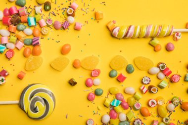 top view of delicious multicolored candies, jellies, sprinkles and lollipops on yellow background