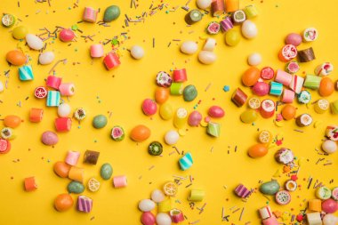 top view of multicolored candies and sprinkles scattered on yellow background