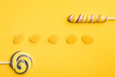 top view of delicious  jellies and multicolored lollipops on yellow background