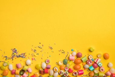 top view of multicolored tasty candies and sprinkles scattered on yellow background with copy space