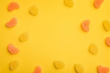 top view of delicious orange and lemon jellies scattered on yellow background