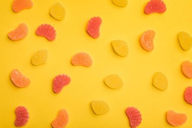 top view of delicious lemon, grapefruit and orange jellies scattered on yellow background