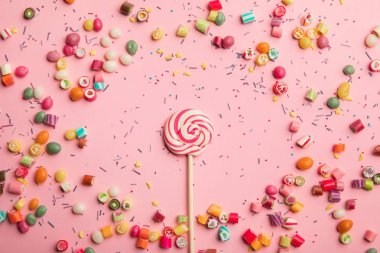 top view of delicious swirl lollipop on wooden stick with scattered caramel candies and sprinkles around on pink background