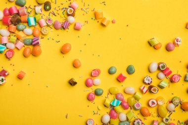 top view of multicolored tasty sweets scattered on yellow background with copy space