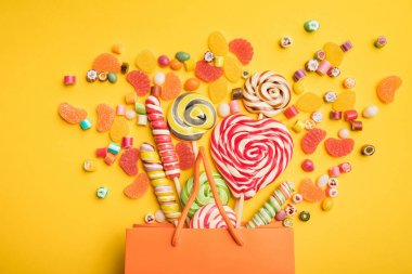 top view of tasty multicolored candies scattered from paper bag on bright yellow background