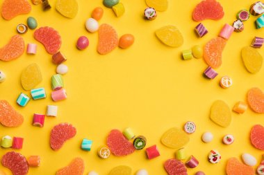 top view of multicolored tasty caramel and fruit jelly candies scattered on yellow background with copy space