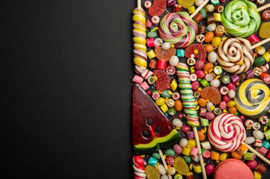 top view of delicious multicolored candies on black background with copy space