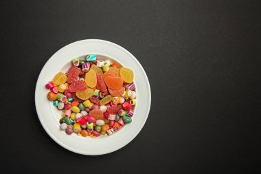 top view of delicious multicolored caramel candies and citrus jellies in white plate on black background with copy space