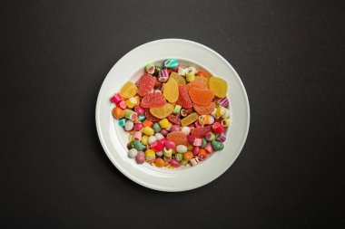 top view of delicious multicolored caramel candies and citrus jellies in white plate on black background