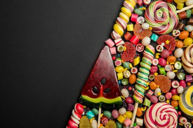 top view of delicious multicolored sweets on black background with copy space
