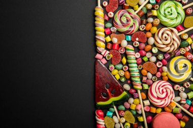 Top view of delicious multicolored sweets on black background stock vector