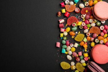 top view of delicious multicolored sweets, sprinkles and macarons on black background