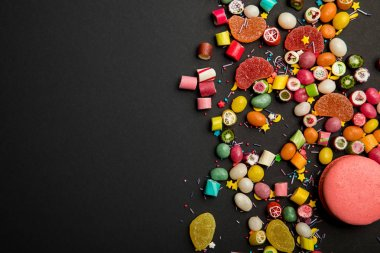 top view of delicious multicolored candies, sprinkles and macarons on black background
