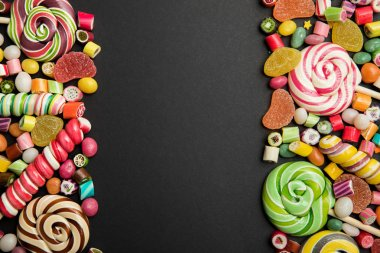 top view of tasty multicolored sweets on black background with copy space