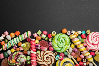 Top view of tasty multicolored caramel sweets and lollipops on black background with copy space stock vector