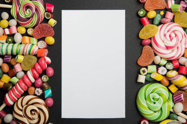 top view of tasty multicolored caramel sweets and lollipops around white empty card on black background with copy space