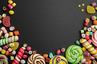 top view of delicious multicolored swirl and round lollipops, candies, jellies and sprinkles on black background