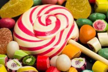 close up view of bright lollipop among fruit caramel multicolored candies