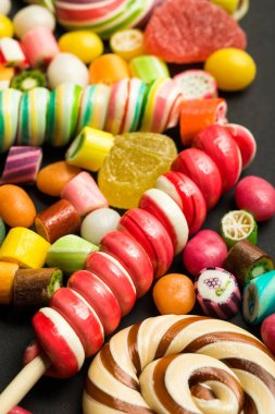 close up view of bright swirl lollipops among fruit caramel multicolored candies