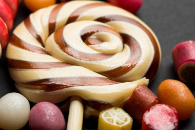 close up view of lollipop among caramel multicolored candies on black background