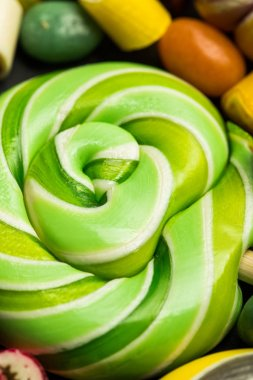 close up view of swirl green tasty shiny sweet lollipop