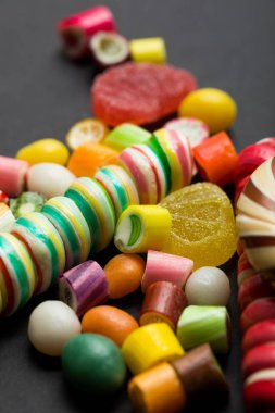 selective focus of delicious multicolored caramel and jelly candies on black background