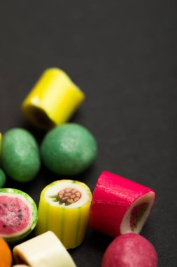 selective focus of delicious multicolored fruit caramel candies on black background