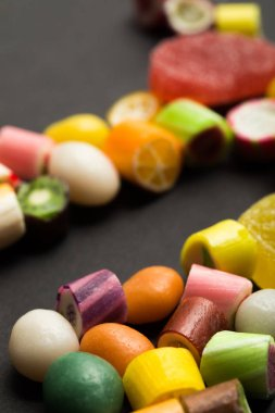 selective focus of delicious multicolored fruit caramel sweets on black background
