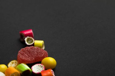 delicious multicolored fruit caramel sweets on black background with copy space