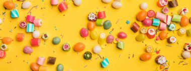 panoramic shot of multicolored candies and sprinkles scattered on yellow background
