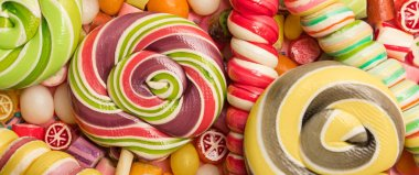 panoramic shot of bright round and swirl lollipops on fruit caramel candies