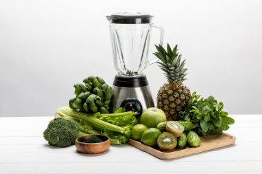 blender near green fresh vegetables and tasty fruits on white