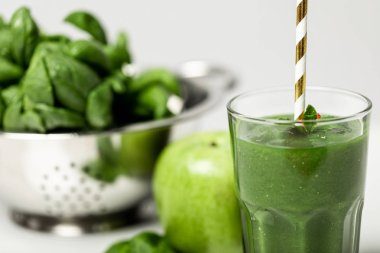 selective focus of tasty green smoothie in glass with straw near spinach leaves and apple on white