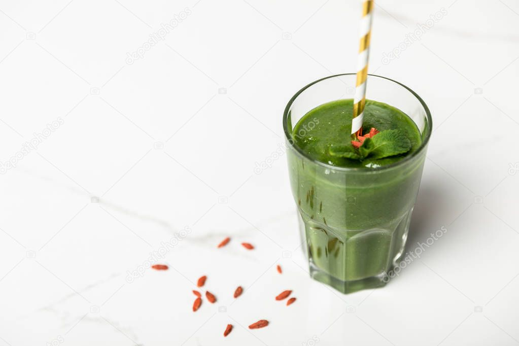 Selective focus of tasty smoothie with goji berries and mint in glass with straw on white stock vector