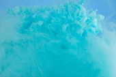 Photo Close up view of turquoise smoky paint swirls isolated on blue