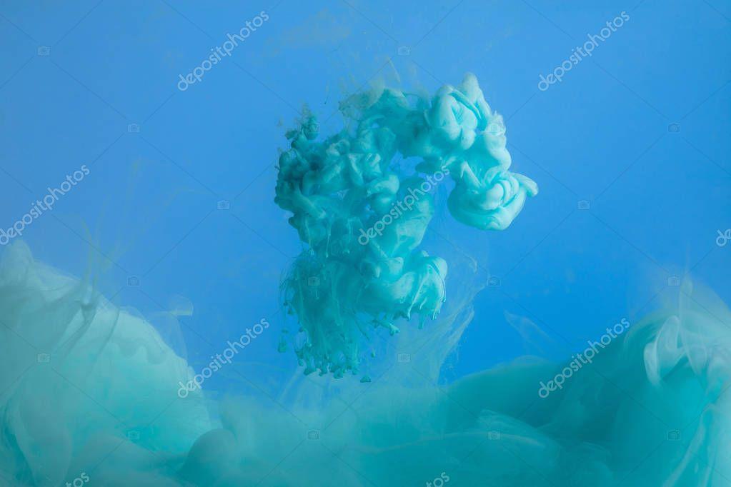 Close up view of turquoise paint splash isolated on blue