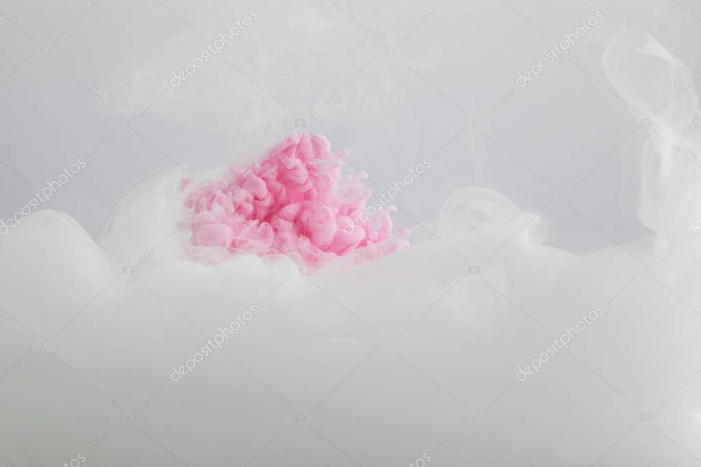 Close up view of pink and white paint mixing isolated on grey