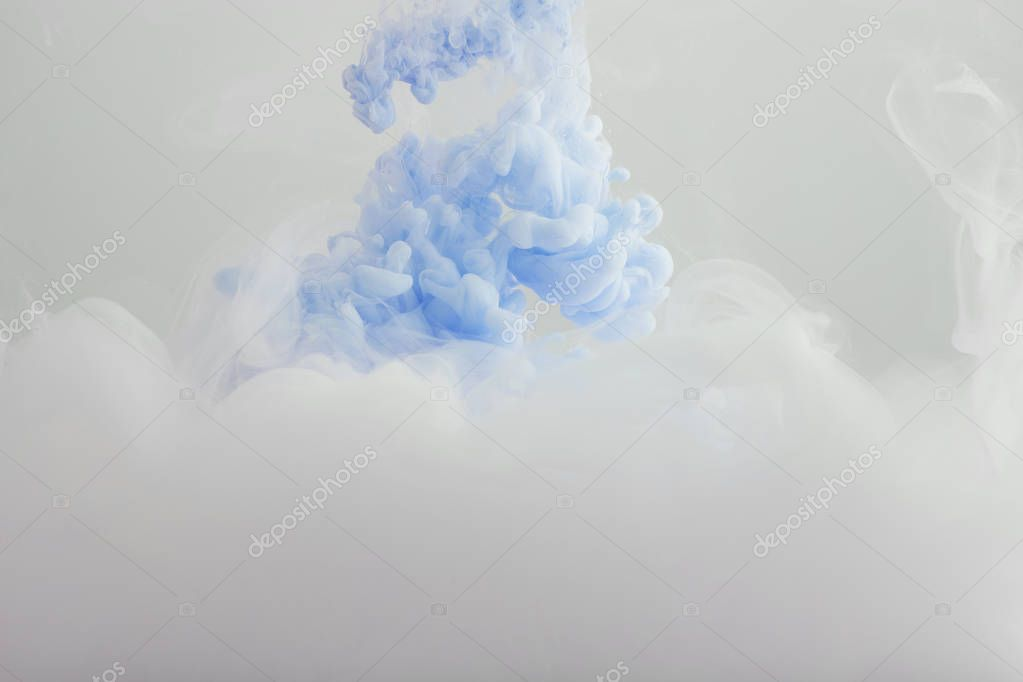 Close up view of light blue and white paint swirls isolated on grey