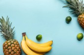 top view of whole ripe pineapples, bananas and limes on blue background with copy space