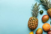 top view of ripe exotic fresh fruits on blue background with copy space