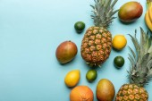 top view of exotic fruits on blue background with copy space