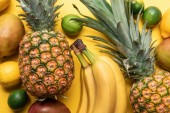 top view of whole ripe bananas, pineapple, citrus fruits and mango on yellow background