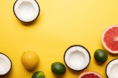 top view of citrus fruits and coconuts on yellow background with copy space