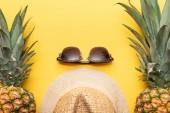 felülnézet Szalmakalapot és napszemüveg közelében ananász a sárga háttér