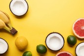 top view of citrus fruits, bananas and coconuts on yellow background with copy space