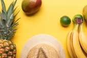 top view of straw hat near pineapple, bananas, limes and mango on yellow background